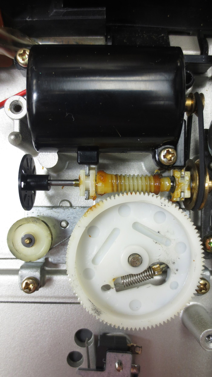 Technics SL 10 Turntable - An overview of the arm motor. The motor is the black cylinder at the tp of the image; this actuates the worm-drive via a small flat belt. The thread drive (lower left) is kept in tension by the spring seen at the bottom of the large nylon gear.